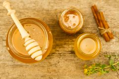 Glass jars of fresh honey with drizzler, cinnamon, flowers on wooden background, top view Stock Image