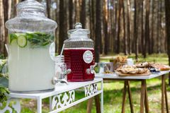 Glass jars with fresh lemonade and snacks on wooden tables. Wedd. Ing party bar in forest Royalty Free Stock Photo