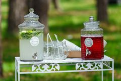 Glass jars of fresh lemonade on wedding candy bar. Summer party. And reception in forest Royalty Free Stock Photography