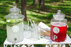 Glass jars of fresh lemonade on wedding candy bar. Summer party. And reception in forest Stock Photography