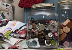 Jars of buttons. Glass jars full of shapes and colors of buttons in a craft room Royalty Free Stock Photos