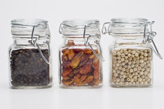 Glass jars full of spices. Some glass jars with peppercorns and chilli stock photo