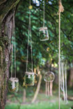 Glass jars hanging on tree. A candle in a glass jars with leaves hanging on a tree in the garden stock photos