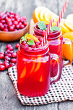 Glass  jars of  homemade juice with orange  slices and wild cranberry Royalty Free Stock Images
