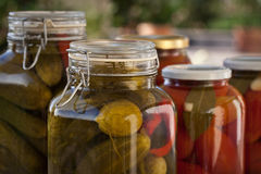 Glass jars of homemade tomatoes and cucumbers. Glass jars of homemade canned tomatoes and cucumbers Stock Images
