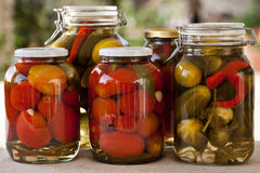 Glass jars of homemade tomatoes and cucumbers. Glass jars of homemade canned tomatoes and cucumbers Stock Photo