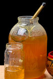 Glass jars with honey and a wooden spoon Royalty Free Stock Photography