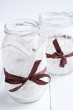 Glass jars with laces and brown ribbons. Stock Photography