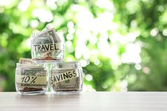 Glass jars with money for different needs on table. Against blurred background stock photos
