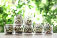 Glass jars with money for different needs on table. Against blurred background royalty free stock photo