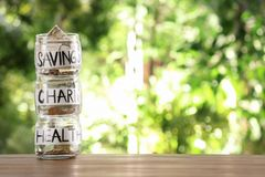 Glass jars with money for different needs on table against blurred background. Space for text stock images