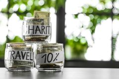 Glass jars with money for different needs on table against blurred background. Space for text stock image