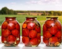Canned tomatoes in large glass jars. Royalty Free Stock Photography