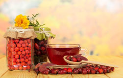 In glass jars  rowan berries, wild rose and cup  tea. Stock Image