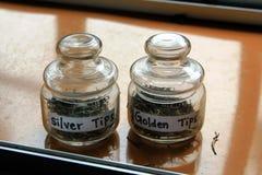 Glass jars with tea. Golden tea. Silver tea stock images