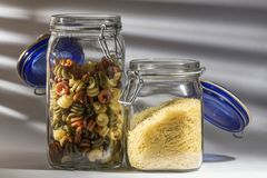 Glass jars with two types of pasta, noodles and spirals. Two glass jars, one with vegetable pasta in the form of spirals and another lower one with fine noodles stock photo