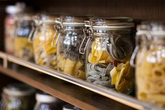 Glass jars with various varicoloured types of pasta Stock Photos