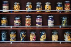Glass jars with various varicoloured types of pasta. On the wooden shelves are glass jars with various varicoloured types of pasta, spaghetti, beans, cereals for Royalty Free Stock Photo