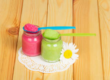 Glass jars with vegetables, fruit puree, spoon on ight wood. Glass jars with vegetables, fruit puree, plastic spoon and daisy on the background of light wood Stock Photography