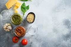 Free Glass Jars With Red And Green Pesto And Cooking Italian Recipe Ingredients Parmesan Cheese, Basil Leaves, Pine Nuts, Olive Oil, Royalty Free Stock Images - 184152339