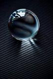 Glass jordklot eller droppe av vatten på ett korrugerat papper för mörk grafit Rengöring och sken royaltyfria foton