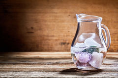 Glass jug with assorted healing stones in water Royalty Free Stock Photo