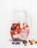 Glass jug with berries water and ice cubes on white wooden background Royalty Free Stock Images