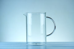 Glass jug. On a blue background stock photos