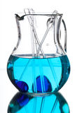 Glass jug with blue water and the reflection in the mirror Stock Images