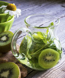 Glass jug with cold green tea  kiwi slices and oregano on wooden gray background Stock Image