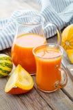 Jug and cup of pumpkin juice and pumpkins. stock photos