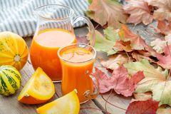 Glass jug and cup of pumpkin juice, pumpkins and fallen maple le stock images