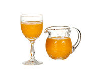 Glass and jug filled with orange juice. Cut glass isolated goblet and jug filled with fresh orange juice royalty free stock photo