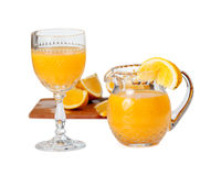 Glass and jug filled with orange juice. Cut glass isolated goblet and jug filled with fresh orange juice with orange slice on edge of jug royalty free stock image