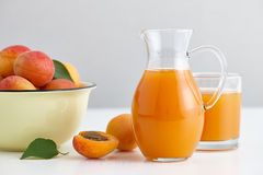 Glass jug with fresh juice and ripe apricots bowl stock image