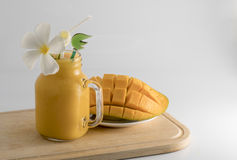 Glass and jug full of fresh cold mango juice. Closeup of fresh mango fruit and mango juice isolated in white background Stock Photo