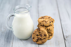 Glass jug with milk and chocolate chip cookies on wooden background Royalty Free Stock Photography