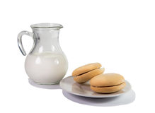 Glass jug with milk and cookies on a plate. Royalty Free Stock Images
