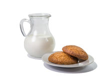 Glass jug with milk and cookies on a plate. Royalty Free Stock Photo