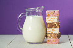 Glass jug of milk and Turkish sweet delights. On purple and white wooden backgrounds Stock Image