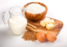 Glass jug with milk, wheat seeds, flour and two eggs Stock Images
