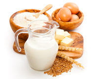Glass jug with milk, wheat seeds, flour and two eggs Stock Photo