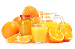 Glass and jug of orange juice, jar of jam and fruits Stock Photography