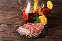 A plate of prosciutto with fresh green leaves of mint, a glass of fruit beverage and orange on a wooden background. Royalty Free Stock Images