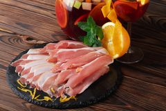 A plate of prosciutto with fresh green leaves of mint, a glass of fruit beverage and orange on a wooden background. Royalty Free Stock Photography