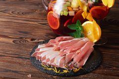 A plate of prosciutto with fresh green leaves of mint, a glass of fruit beverage and orange on a wooden background. Stock Photography