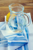 Glass jug with water and lemon on kitchen towel and over wooden background Stock Images