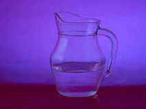 Glass jug with water on purple, mauve background. Stock Photos