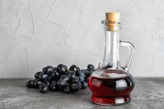 Glass jug with wine vinegar and fresh grapes. On gray table royalty free stock images