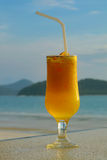 Glass of juice. Against seascape Royalty Free Stock Photo